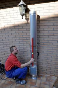 Herr Bläßer bei der Montage des Außenwandkamins. Daran angeschlossen wird ein Pelletkaminofen.